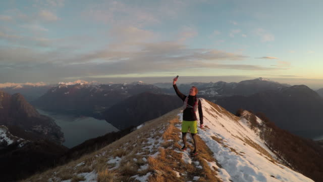 male trail runner searches for cell service on snowy mountain ridge above lake at sunset - mountain top filmów i materiałów b-roll