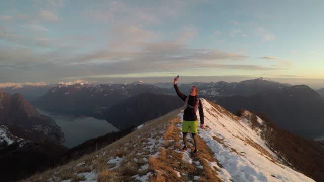 남성 트레일 러너 일몰에 호수 위에 눈 덮인 산 능선에 셀 서비스에 대 한 검색 - mountain top 스톡 비디오 및 b-롤 화면