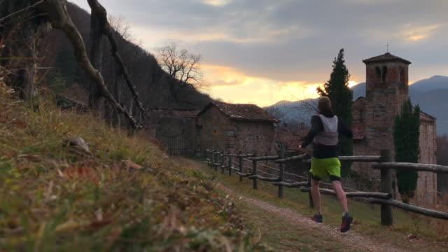 erkek iz runner adımlar arka plan kilisede ile iz aşağı - uzun adımlarla yürümek stok videoları ve detay görüntü çekimi
