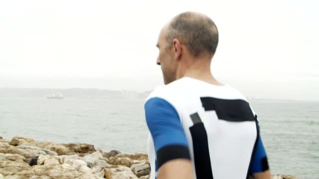 male triathlete jogging along promenade at sea - triatleta video stock e b–roll