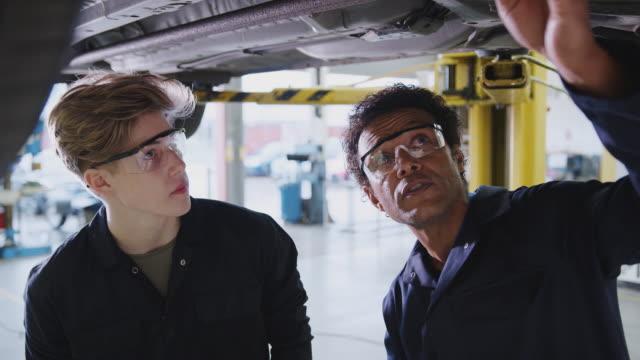 мужской репетитор со студентом глядя под автомобилем на гидравлический пандус на автомеханик конечно - моторное транспортное средство стоковые видео и кадры b-roll