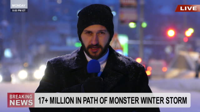 Male TV reporter presenting the snow situation in town Male TV reporter reporting snow storm. Wears warm clothes, with cup, beard. Looking at camera. Street traffic on background. meteorology stock videos & royalty-free footage