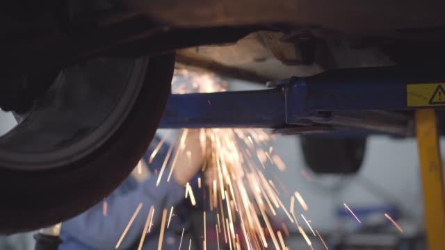 manliga oigenkännliga kaukasiska auto mechanic svets bil. professionellt arbete i reparationsverkstad. yrke, yrke, livsstil. - garage bildbanksvideor och videomaterial från bakom kulisserna