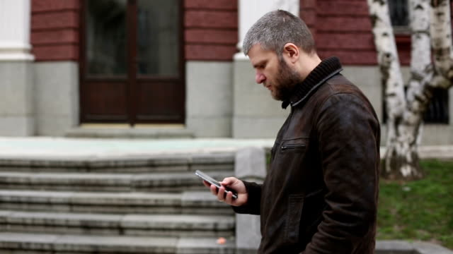 Male using cell phone in the city video