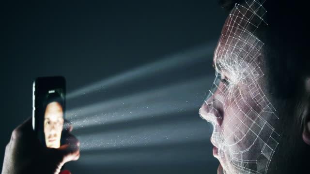 male using latest smartphone technology for a biometric facial recognition unlock - идентификация личности стоковые видео и кадры b-roll
