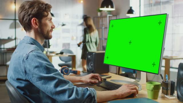 l'editor video maschile con camicia barba e jeans funziona sul suo personal computer con un grande display mock up a schermo verde. lavora in un loft dell'ufficio. altre collega creative femminili camminano sullo sfondo. - designer professionista video stock e b–roll