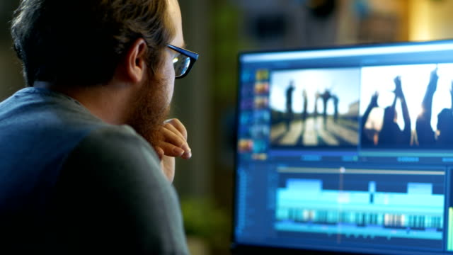 男性のビデオ編集の映像と音の 2 つの表示の彼の個人的なコンピューター上の取り扱い彼は涼しいオフィス ロフトで動作します。 - 編集者点の映像素材/bロール