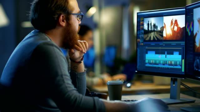 男性のビデオ編集の映像と音の 2 つの表示の彼の個人的なコンピューター上の取り扱い彼は他のクリエイティブな人々 と涼しいオフィス ロフトで動作します。 - 編集者点の映像素材/bロール