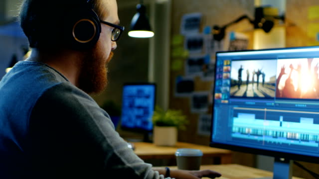 男性のビデオ撮影編集し、彼のパソコンに置く彼のモニターの映像と音をカット/ヘッドフォン。彼のオフィスは現代および創造的なロフト スタジオです。 - 編集者点の映像素材/bロール