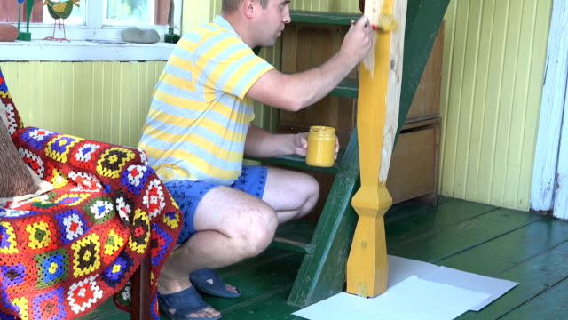 male villager man painting pole in rural garden room with brush. 4K