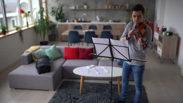 Male violinist rehearsing music piece in living room