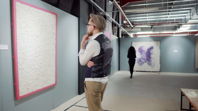 Male visitor is examining painting work of modern abstract artist in exhibition - vídeo