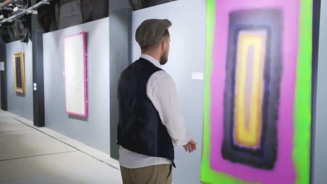 vídeos de stock, filmes e b-roll de o visitante masculino da exposição do artista abstrato moderno está prestando atenção ao retrato - arte, cultura e espetáculo