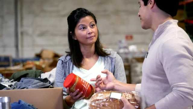 vídeos y material grabado en eventos de stock de voluntario masculino manos abarrotes mujer - food drive