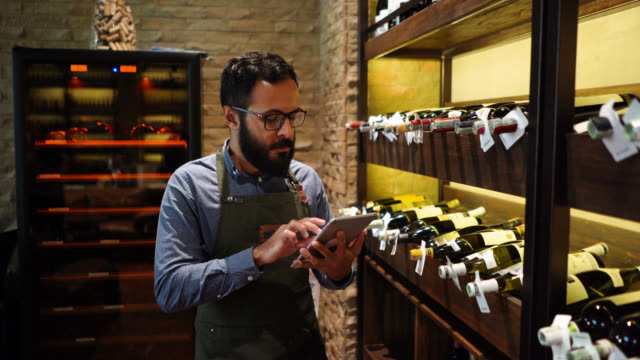 Male waiter doing an inventory of the wine bottles on rack at a restaurant using a tablet