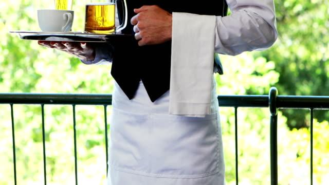 male waiter holding tray with coffee cup and beer mug in restaurant 4k - taca filmów i materiałów b-roll