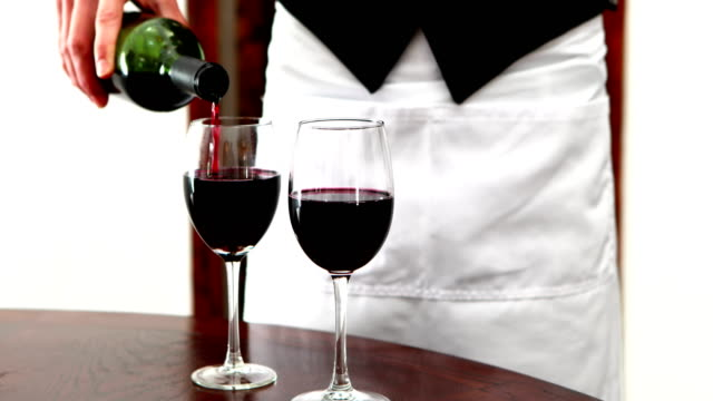Male waiter pouring wine into wine glasses 4k video