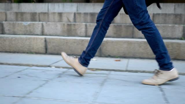 Male walking on the sidewalk near building video