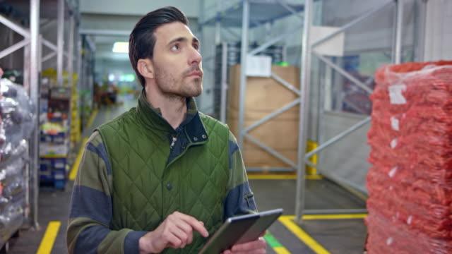 koridorda yürürken raflarda taze ürünlerin envanterini kontrol erkek depo çalışanı - dağıtım deposu stok videoları ve detay görüntü çekimi