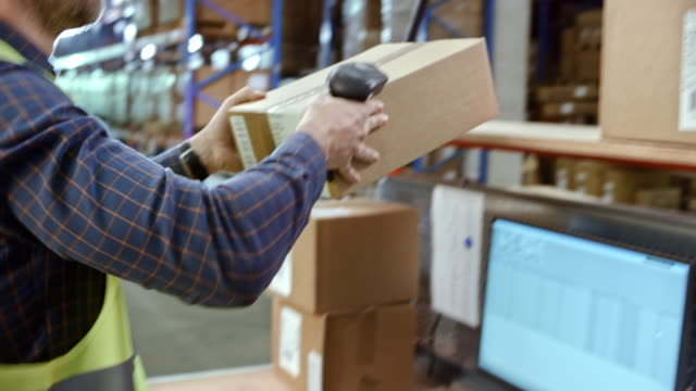 Male warehouse employee scanning packages on a desk in the warehouse with a handheld scanner