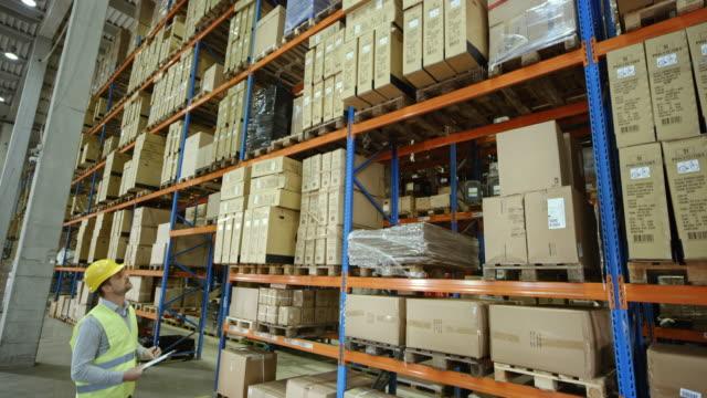 CS Male warehouse supervisor checking the pallet racks in a full warehouse video