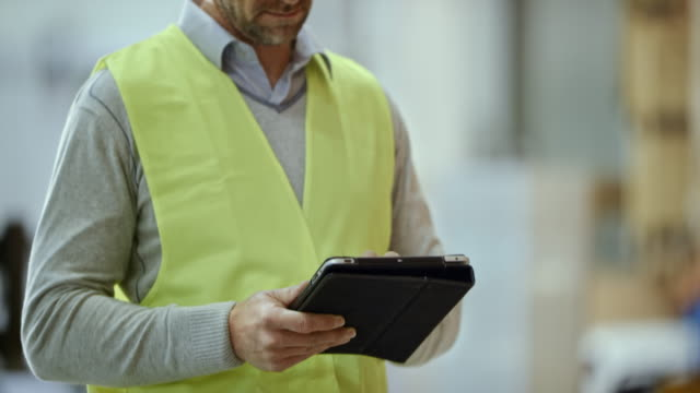 Male warehouse supervisor entering data into the tablet while checking the pallet racks video