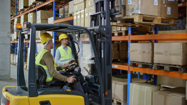 Male warehouse supervisor telling the forklift operator to put the pallet back on the rack in the warehouse video