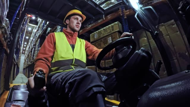 TIME LAPSE Male warehouse worker sitting in the forklift and driving inside the warehouse Time lapse low angle shot of a male warehouse worker sitting in the cabin of a forklift and driving in the warehouse. Shot in Slovenia. forklift stock videos & royalty-free footage