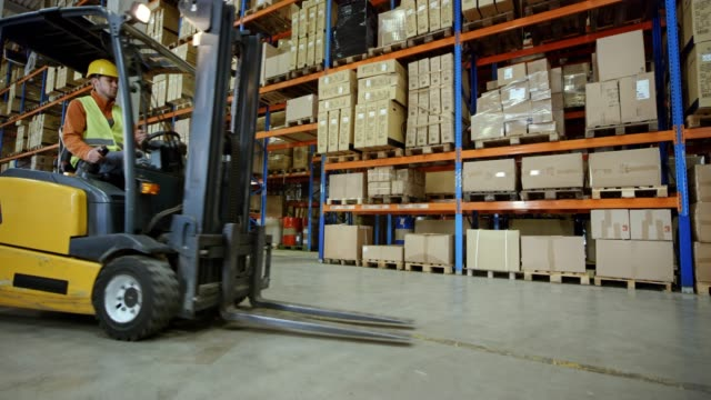 CS Male warehouse worker using a forklift to take a pallet off the rack Wide crane shot of a male forklift operator taking a pallet off the rack in a warehouse. Shot in Slovenia. forklift stock videos & royalty-free footage