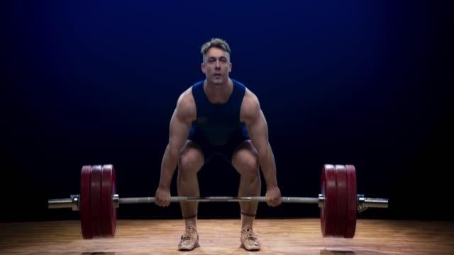männlicher gewichtheber versäumt, die sauberen und ruck-lift bei einem wettbewerb durchzuführen - gewichtstraining stock-videos und b-roll-filmmaterial