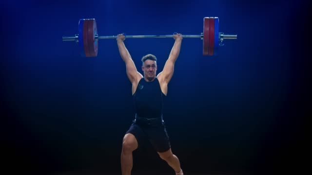 LD Male weightlifter in black outfit performing the clean and jerk to lift the barbell