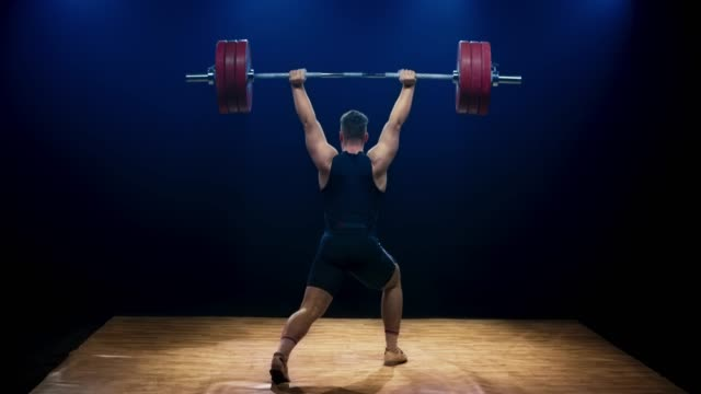 LD Male weightlifter lifting a barbell at a competition