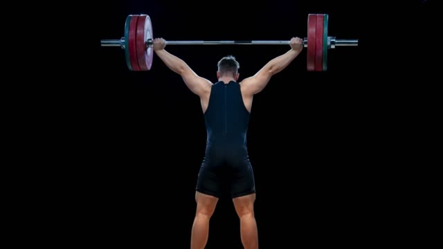 LD Male weightlifter lifting the barbell over his head in one motion