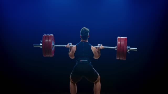 Male weightlifter lifting the barbell with the clean and jerk lift at a competition