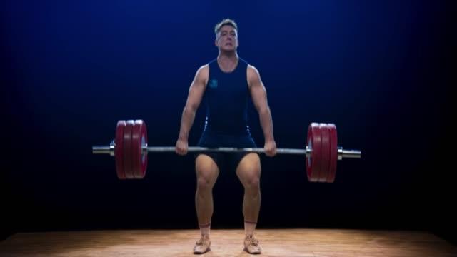 männlicher gewichtheber, der bei einem wettkampf sauber und ruckartig ist - gewichtheben stock-videos und b-roll-filmmaterial