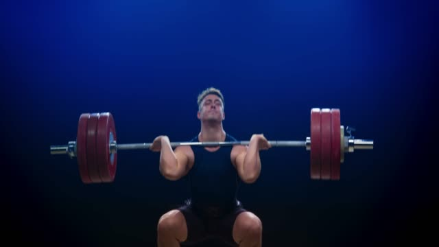 Male weightlifter performing the clean and jerk at a competition
