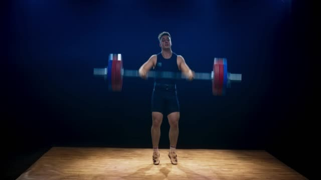 LD Male weightlifter performing the snatch lift to raise the barbell above his head at a competition