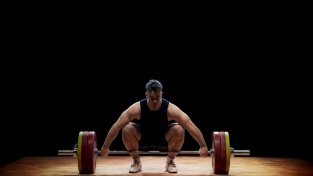 ld male tyngdlyftare höja skivstång med hjälp av ryck hissen vid en tävling - styrketräning bildbanksvideor och videomaterial från bakom kulisserna