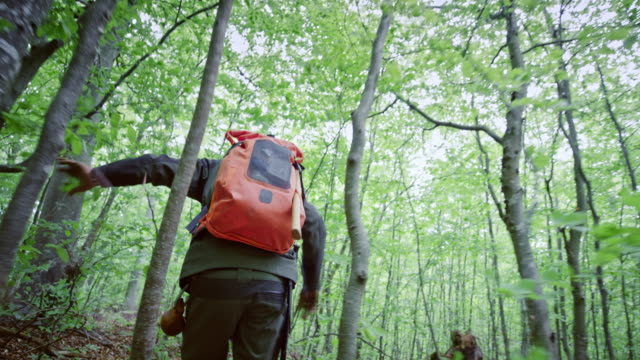 TS Male wilderness survival specialist running through the forest
