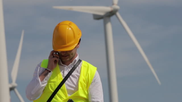 Male wind turbine engineer wearing a yellow safety hat and yellow vest. Makes a phone call Slow motion of a man engineer inspecting the windmill turbines. Concept of: career, problem solving, work and engineering. civil engineering stock videos & royalty-free footage