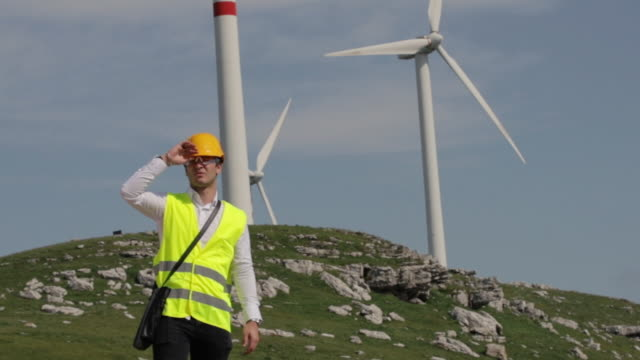 Male Wind Turbine Engineer wearing yellow vest and safety helmet Male wind turbine engineer wearing a white safety hat and yellow vest. civil engineering stock videos & royalty-free footage