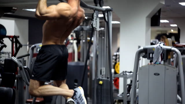Male with an athletic build exercising on bar at gym video