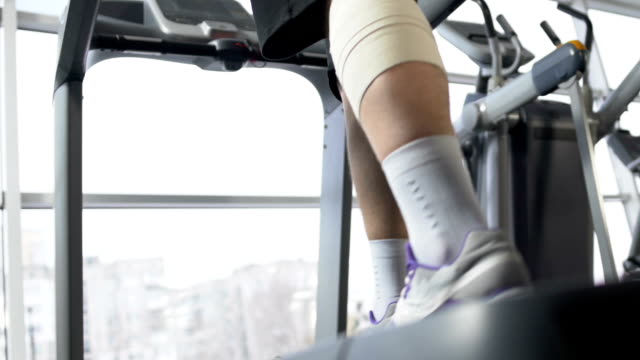 male with injured leg muscle walking on treadmill in gym, recovery, will power - runner rehab gym video stock e b–roll
