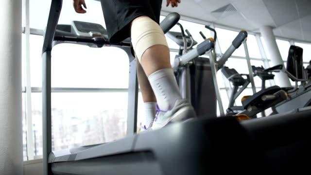 Male with knee bandage slowly walking treadmill, rehabilitation center, recovery video