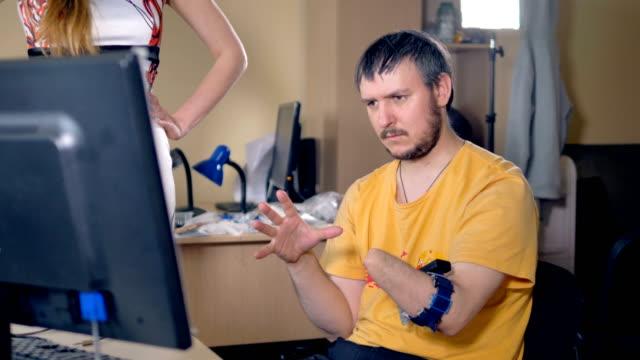 vídeos de stock, filmes e b-roll de homem com o braço amputado usando computador com tecnologia sem fio. 4k. - ortopedia