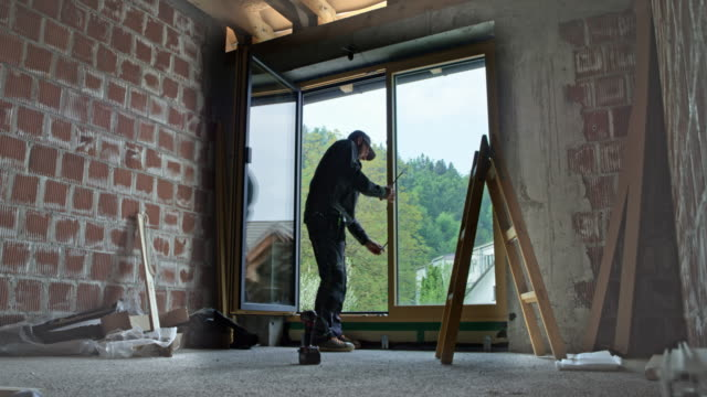 ld male worker adjusting the balcony door after installation - okno filmów i materiałów b-roll