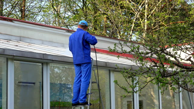 male worker clean window of glass house. video