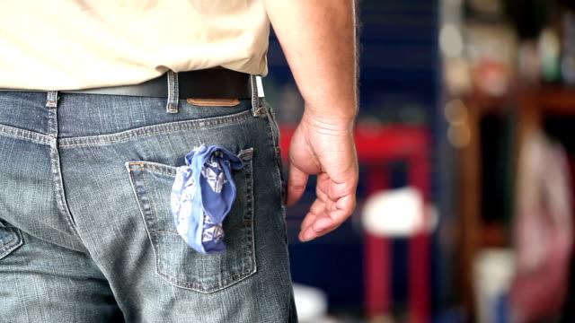 male worker cleaning hands on rag - dżinsy filmów i materiałów b-roll