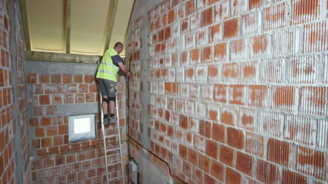 stockvideo's en b-roll-footage met mannelijke werknemer klimmen op de ladder in het huis te installeren van een plastic pijp in in de bakstenen muur - ladder