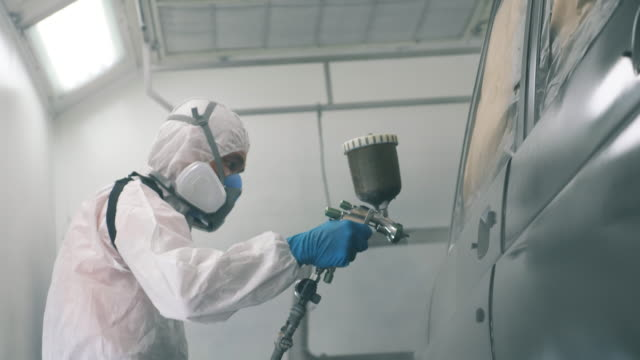 male worker is colouring the automobile with the airbrush. industrial spray painting process. - lucidare video stock e b–roll